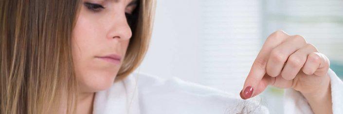 Mulher segurando fio cabelo
